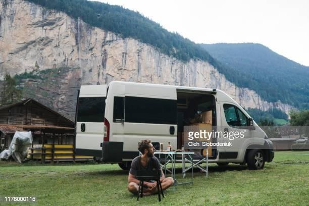 mann grillt burger auf camping in schweizer alpen - camping stock-fotos und bilder