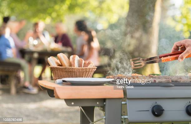 man grilling meat on barbecue grill - bbq stock photos and pictures