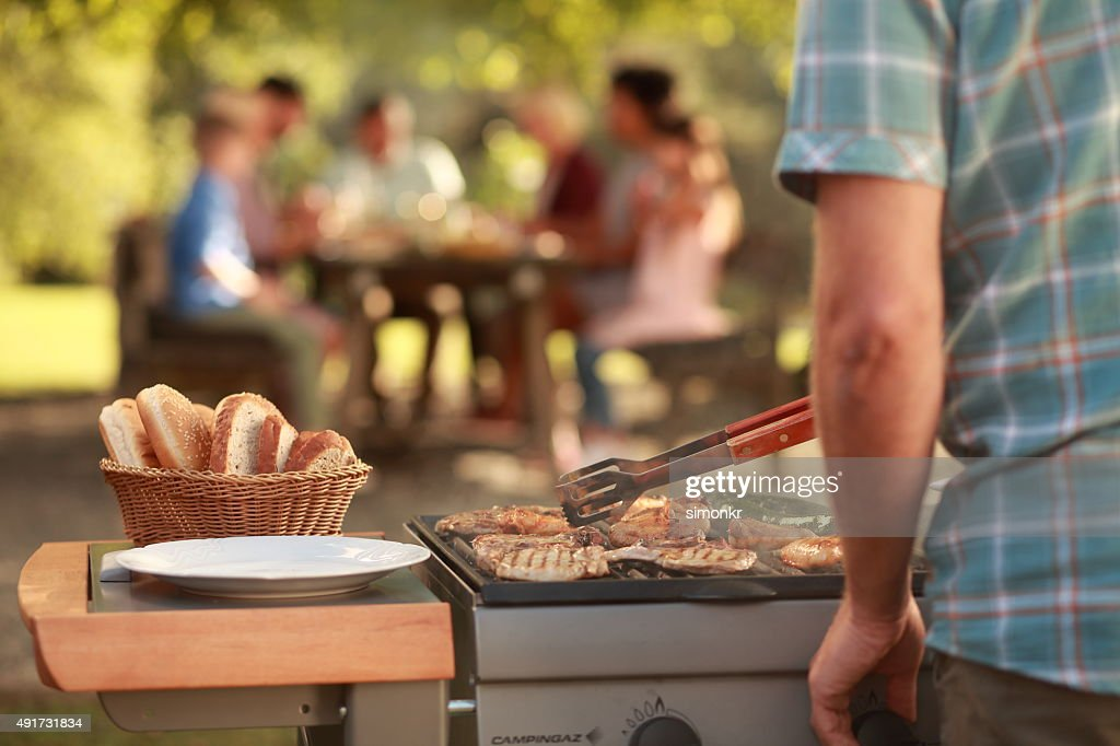 Man grilling meat on barbecue grill : Stock Photo