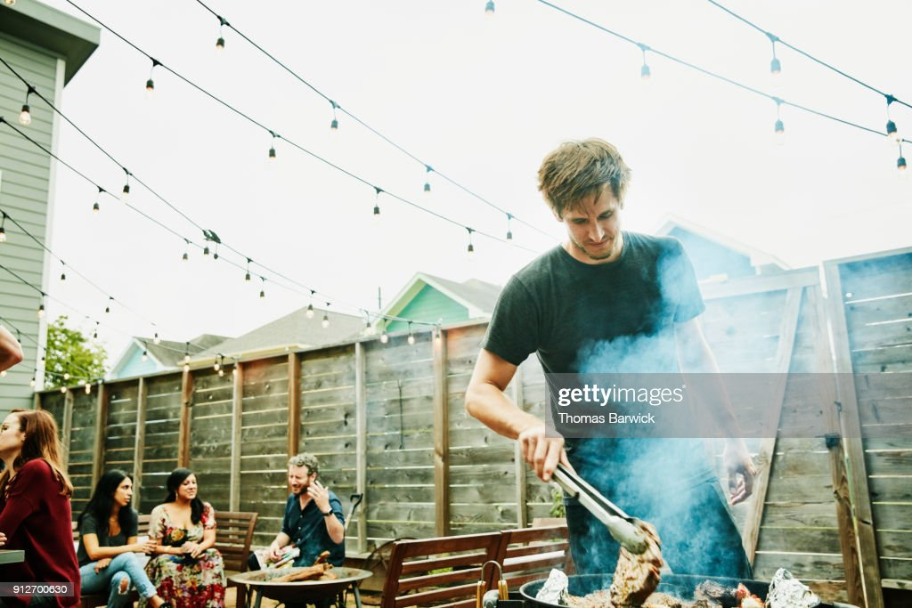 Man grilling steaks for friends at backyard barbecue during party : Stock Photo