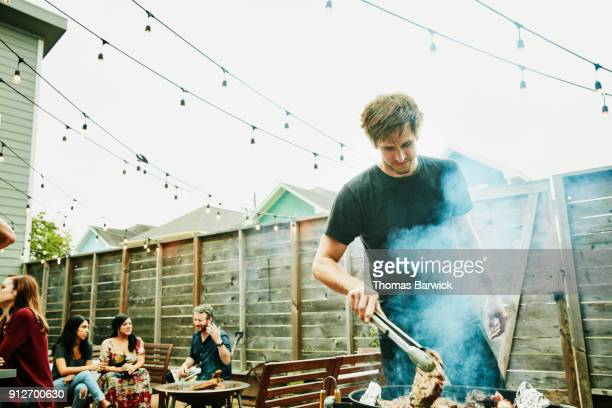 man grilling steaks for friends at backyard barbecue during party - barbecue social gathering stock pictures, royalty-free photos & images