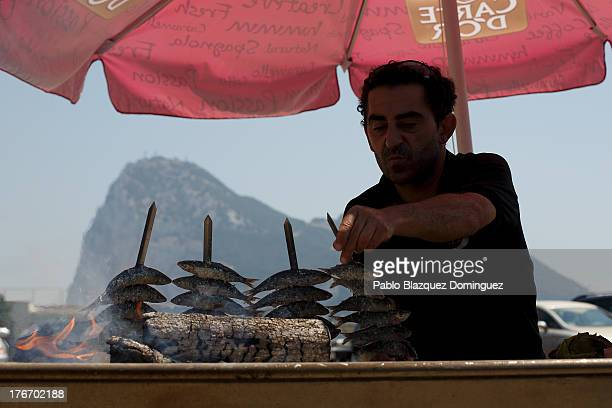 A man grills sardines at a beach restaurant as the Rock of Gibraltar is seen on the back on August 17 2013 in Linea de la Concepcion Spain British...