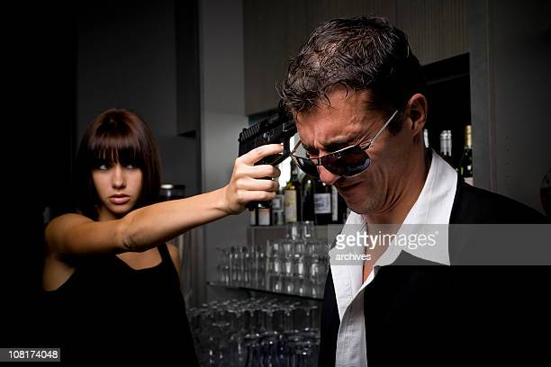 man grimacing while woman holds gun to his head - film noir style stock photos and pictures