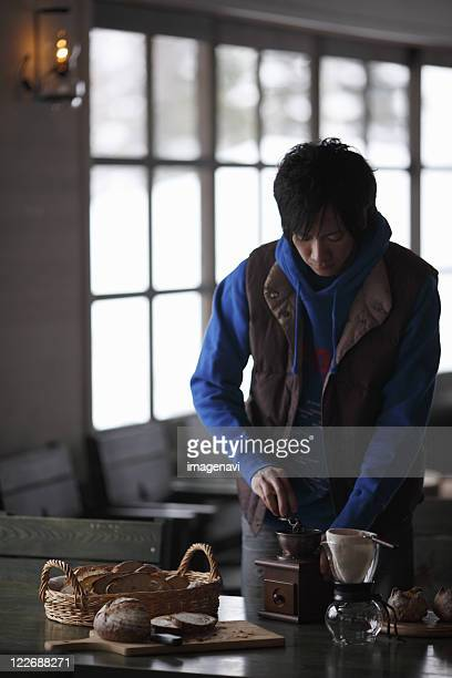A man grinding the coffee