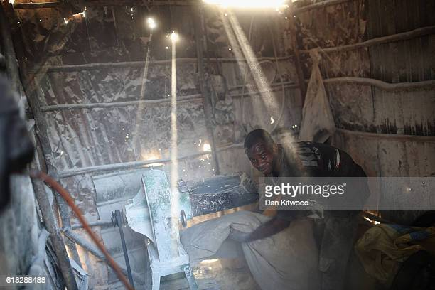 A man grinds rice in a market area on November 19 2015 in Conakry Guinea Guinea is currently counting down the necessary 42 days period required...