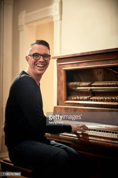 man grinning and playing piano - heshphoto imagens e fotografias de stock