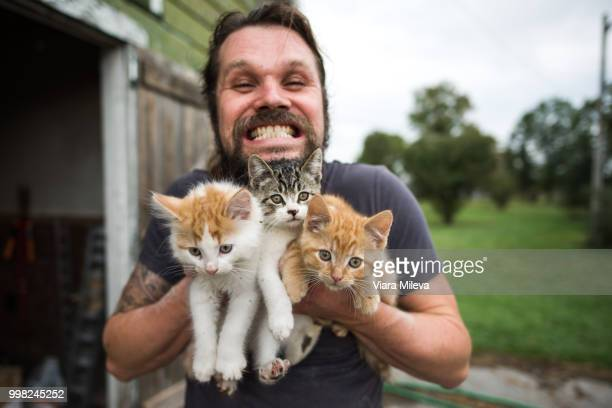Man grinning with three kittens in arms