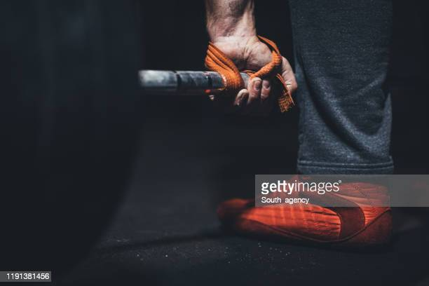 man gripping a barbell - strap stock pictures, royalty-free photos & images