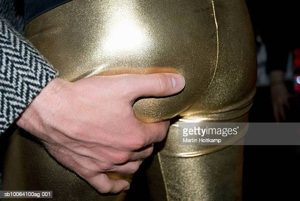 Man gripping woman's buttock, mid section, close-up of hand