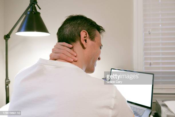 man grips back of neck in pain while working on computer - injured stock pictures, royalty-free photos & images