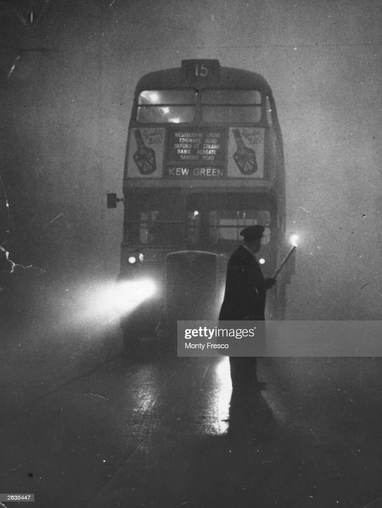 A man guiding a London bus through thick fog with a flaming torch.