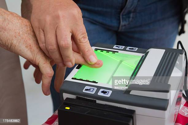 man guiding another in using a fingerprint scanner - biometrics stock photos and pictures
