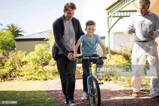 Man guiding son in cycling with grandpa on pathway