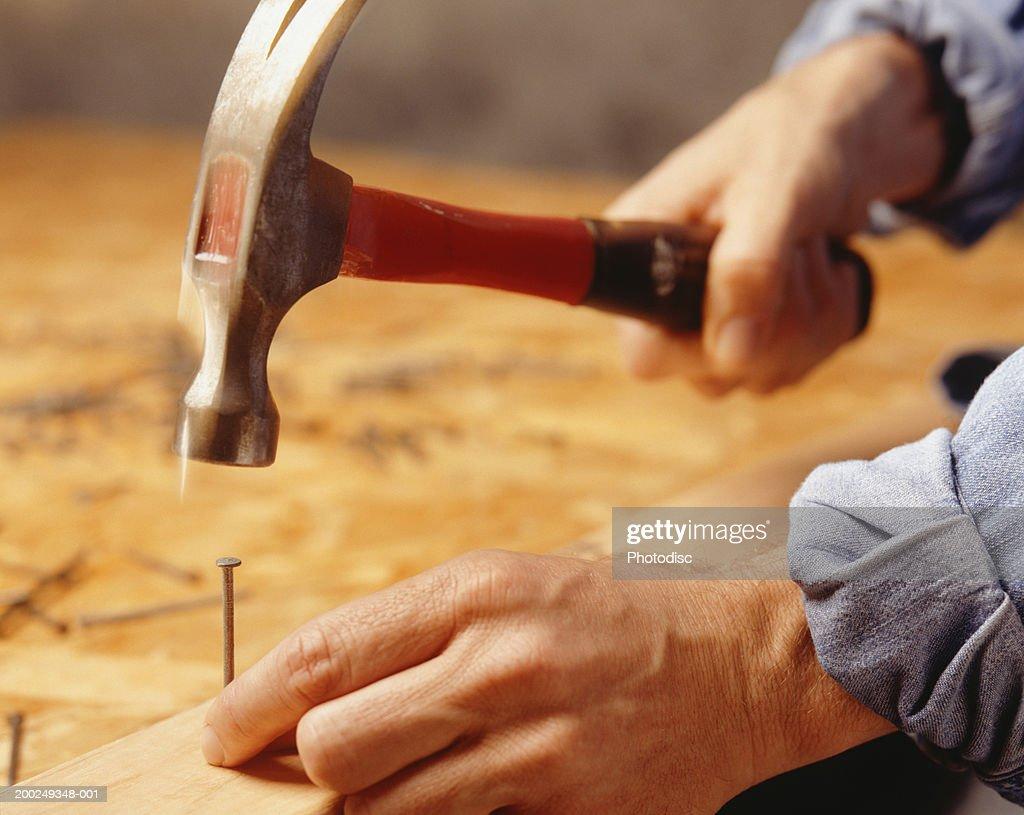 Man hammering nail, (Close-up) : Stock Photo
