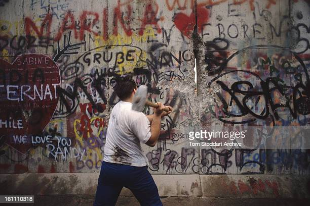 A man hammers at the wall in Berlin during the Fall of the Berlin Wall 10th November 1989