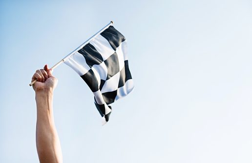 Man hand holding checkered flag in the wind 1094767414