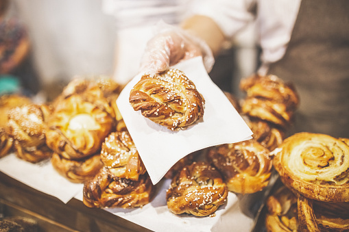 Man hand holding golden colored pastry rolls in bakery. 1169533855