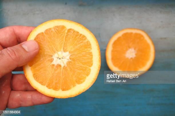 man hand holding slice of fresh orange fruit over a green wooden table - rafael ben ari bildbanksfoton och bilder