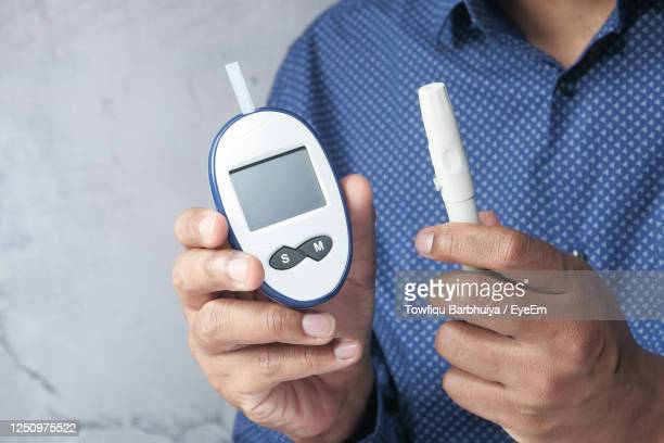 man hand measuring diabetic glucose level at home. - diabetes stock pictures, royalty-free photos & images