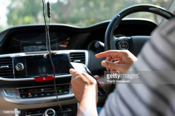 Man hand on use mobile in car, used GPS to drive the car.