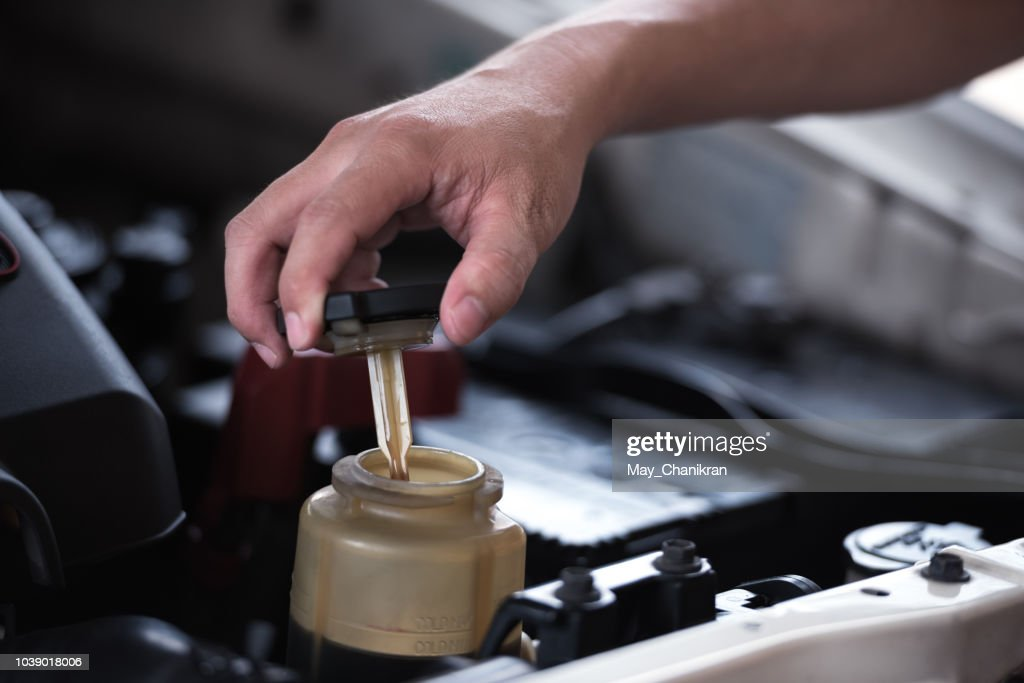 Man hand open power steering cap up for checking level of power steering fluid in the system, car maintenance service concept. : Stock Photo