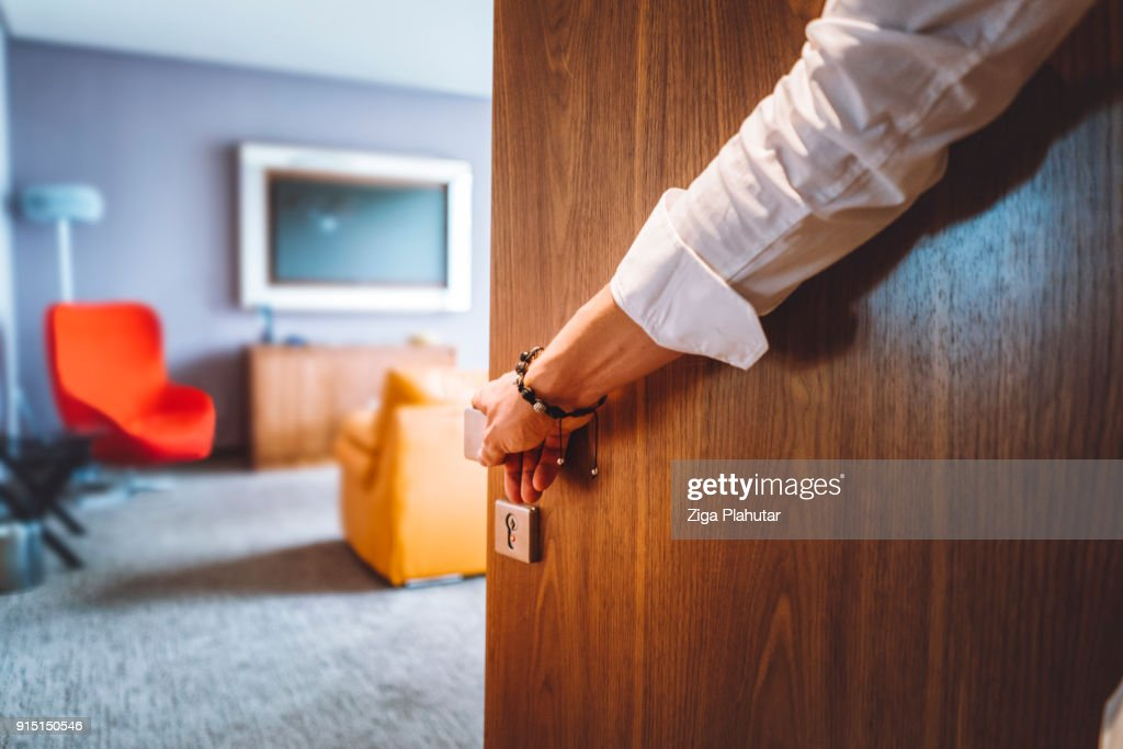 Man hand opening the door of the luxurious hotel room : Stock Photo