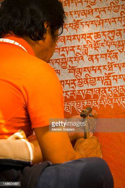 man handcrafting sacred scriptures on a red painted rock on tashilhunpo lingkhor sacred path. - merten snijders stockfoto's en -beelden