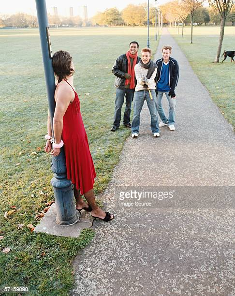 man handcuffed to lamp post being laughed at - bound in high heels stock photos and pictures