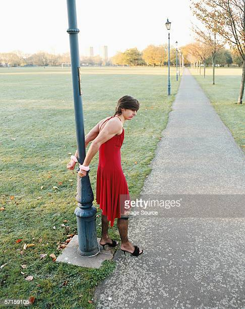 man handcuffed to lamp post wearing red dress - transvestite stock photos and pictures