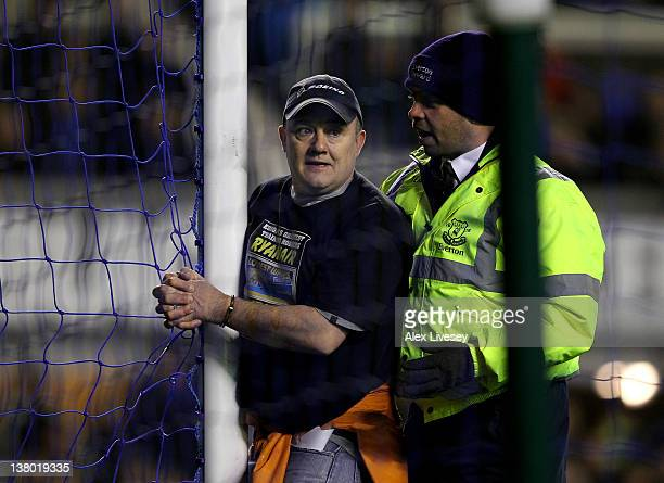 A man handcuffs himself to the goal posts during the Barclays Premier League match between Everton and Manchester City at Goodison Park on January 31...
