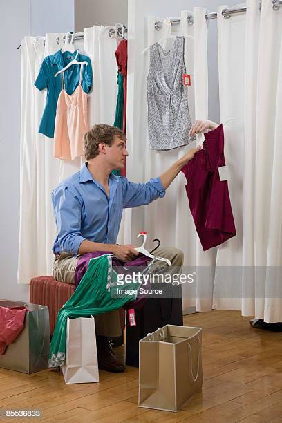 A man handing a woman clothes