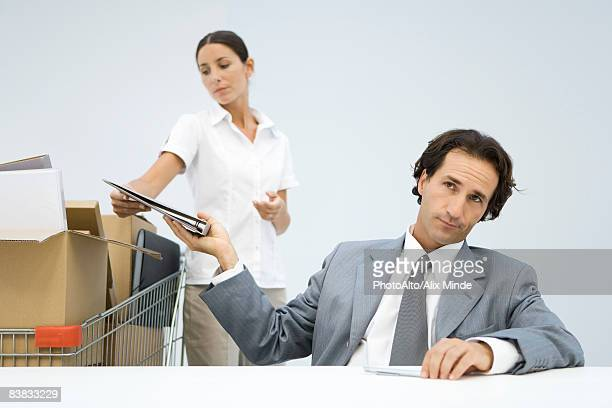 Man handing binder back to assistant, shopping cart full of boxes nearby