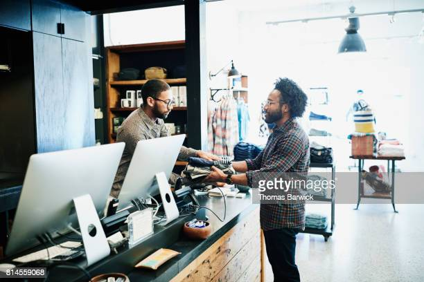 Man handing clothes to shopkeeper at register in mens clothing boutique