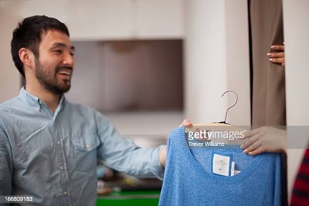 Man handing clothes to someone in fitting room