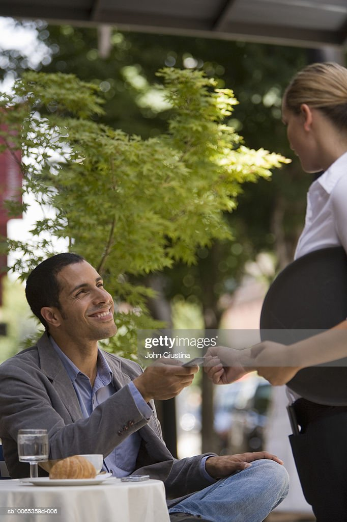 Man handing credit card to waitress at outdoor cafe : Foto stock