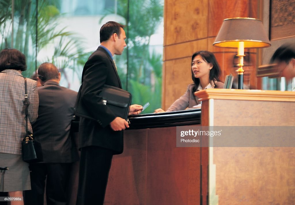 Man handing hotel receptionist into credit card : Stock Photo