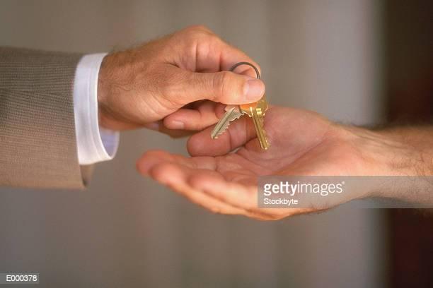 Man handing keys to second man, hand shot