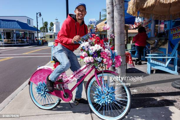 A man handing out brochures on a pink bicycle covered in flowers on Dodecanese Boulevard