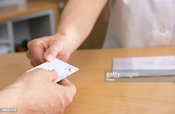 man handing out health insurance card, midsection - health insurance stock pictures, royalty-free photos & images