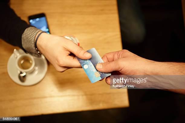 Man handing over credit card in restaurant