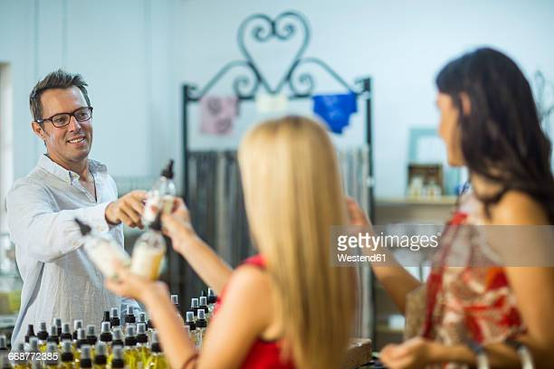 Man handing over perfume bottle to woman in shop