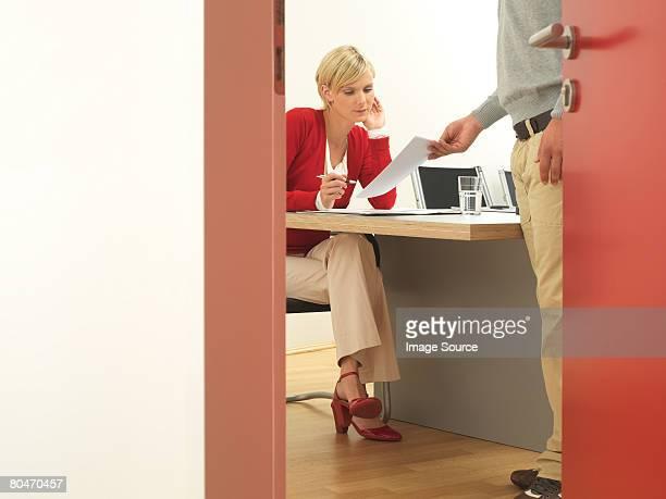 A man handing paperwork to a woman