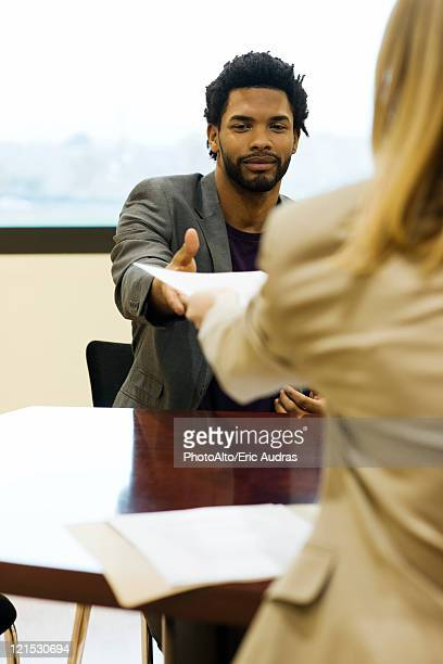 Man handing prospective employer his resume during job interview