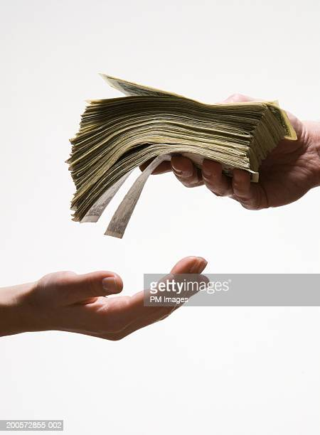 Man handing woman stack of US dollar banknotes, close-up