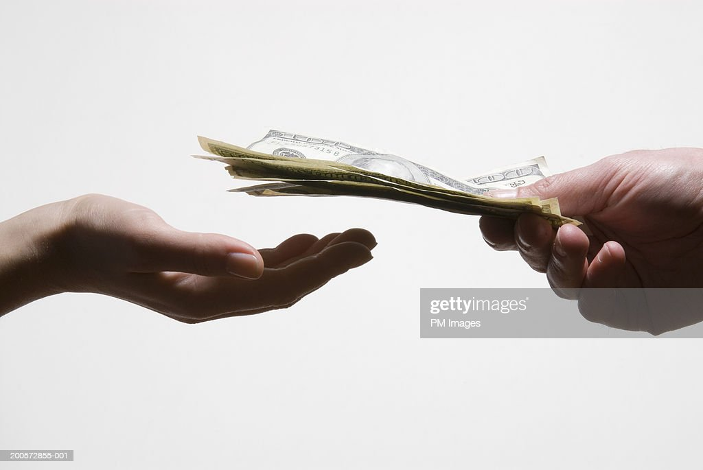 Man handing woman US dollar banknotes, close-up : Stock Photo