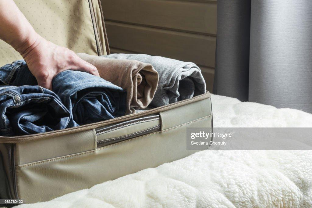 Ein Mann Verarbeitet Die Dinge. Offenen Koffer Mit Kleidung Auf Dem Bett.  Blick Auf Das Schlafzimmer.