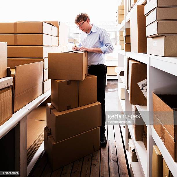 Man handling paperwork in a warehouse