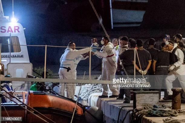 A man hands a baby to another as migrants are assisted as they disembark a boat after being rescued by the Ocean Viking rescue ship on Italy's...