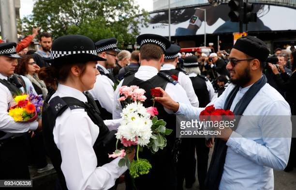 A man hands a flowers to a police officer during a gathering south of London Bridge in London on June 7 following the June 3 terror attack on London...