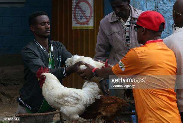 A man hands a rooster to another man at the Sholla bazaar ahead of Easter celebrations in Addis Ababa Ethiopia on April 07 2018 Orthodox Christians...